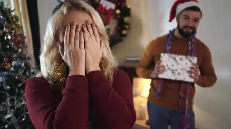 cappello rosso : Blond Caucasian girl with eyes closed with hands trying to look back at man standing with gift box. Husband making surprise present for his wife on Christmas eve