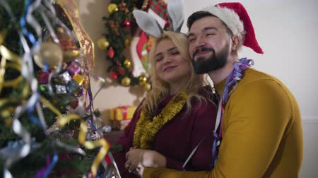 appendere : Happy young Caucasian couple hugging in front of Christmas tree and smiling. Handsome man and blond woman resting at home on New Years eve. Happiness, leisure, relaxation, holidays season