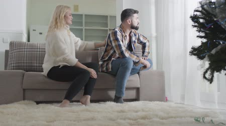 resentment : Young blond woman caressing mans back and talking. Offended bearded guy sitting on sofa with his back to wife or girlfriend. Guilty girlfriend or wife apologizing