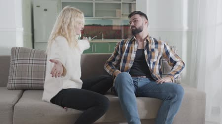 cheated : Front view of young Caucasian couple yelling at each other as sitting on couch at home. Handsome man and beautiful woman arguing indoors. Problems. misunderstanding, communication problems