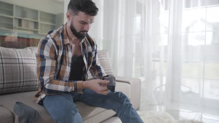 cheirando : Bearded Caucasian man looking for clean socks as sitting on couch. Guy sniffing sock he found under the sofa, putting it on and leaving. Getting dressed, single man