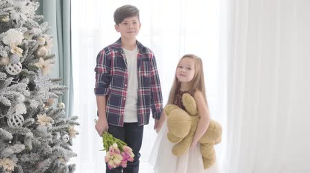 maci : Portrait of Caucasian boy and girl standing together next to the Christmas tree and shaking hands. Brunette boy holding his first loves hand and a bouquet of tulips, little lady holding teddy bear