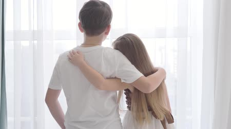 omini : Camera approaching to Caucasian girl and boy standing together in front of the window. Children hugging and looking out. First love, happiness, coziness