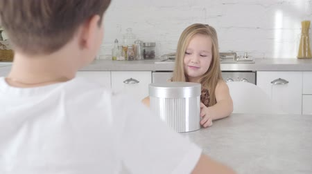 shy girl : Unrecognizable Caucasian boy in white T-shirt giving gift box to pretty little lady. Cute girl taking present and spinning beautiful container. Birthday, Christmas, holiday
