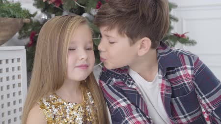 guance : Close-up portrait of Caucasian boy kissing cute girl on cheek under Christmas tree. New Years eve, first love, happiness