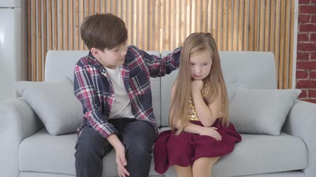 shy girl : Portrait of Caucasian boy stroking cute sad girls head. Friend calming down lady in dress. Relationship, first love, childhood Stock Footage