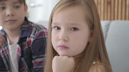 acalmar : Close-up portrait of sad Caucasian girl with brown eyes looking at camera and away as blurred boy caressing her head at the background. Friend calming down upset lady. Friendship, first love, care