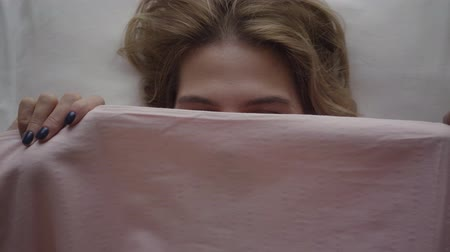 matelas : Close-up of young blond Caucasian woman looking out from under pink blanket and hiding again. Portrait of positive cute girl smiling in the morning. Leisure, resting, relaxation Vidéos Libres De Droits