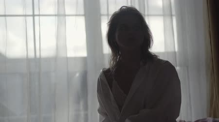 matelas : Blond Caucasian woman in lace underwear and white shirt sitting on bed in front of big window. Beautiful young woman resting in the morning at home. Tranquility, lifestyle, relaxation Vidéos Libres De Droits