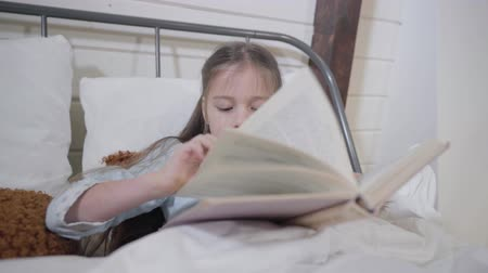 deha : Portrait of pretty Caucasian girl lying in bed and reading book. Smart child going for sleep in the evening. Bedtime, hobby, leisure