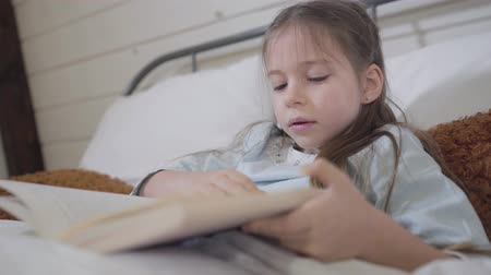 colchão : Close-up of little brunette Caucasian girl reading book in bed. Happy charming child enjoying stories at bedtime. Hobby, lifestyle, leisure Stock Footage