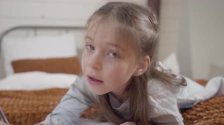 sallama : Camera approaching to cute face of little Caucasian girl lying on bed and writing. Pretty cheerful child looking at camera and shaking finger. Childhood, joy, leisure Stok Video