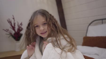 матрац : Camera approaching to cute little Caucasian girl in white bathrobe shaking long curly hair. Pretty kid sitting on bed after shower and smiling. Leisure, lifestyle, relaxation