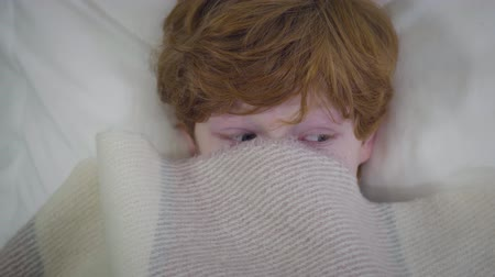 colchão : Close-up of eyes of redhead Caucasian boy with face covered with blanket. Little guy lying in bed and looking around. Childhood, leisure, fun Stock Footage