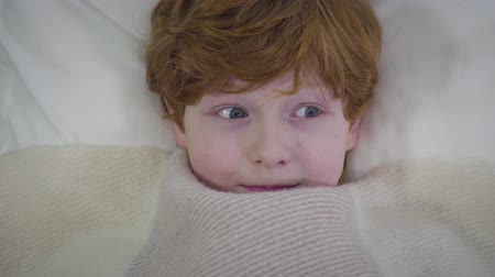 ruivo : Close-up of redhead Caucasian boy with grey eyes lying under blanket and looking around. Little child lying in bed alone. Childhood, leisure, fun