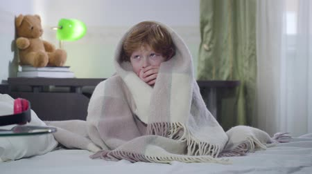 redhair : Portrait of cute little Caucasian boy sitting on bed covered with blanket and looking around. Scared child with red hair left home alone. Childhood, loneliness, fear