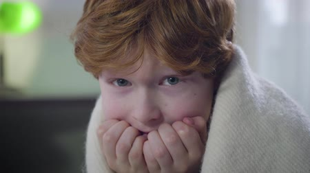 redhair : Close-up of scared Caucasian redhead boy sitting indoors covered with blanket and looking around. Little cute kid left home alone. Childhood, fear, lifestyle Stock Footage