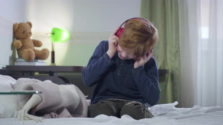 hevesli : Little Caucasian boy with red hair putting on headphones and shaking head emotionally. Cute child listening to rock music indoors. Joy, hobby, lifestyle Stok Video