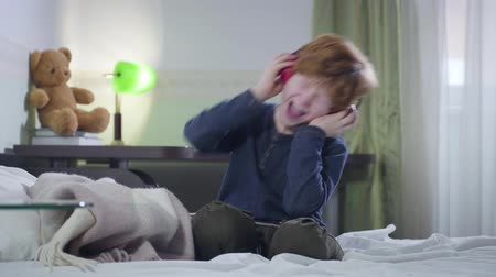 hevesli : Little Caucasian boy shaking head emotionally as listening to rock music in headphones. Cute redhead kid sitting in his room at home and enjoying weekends. Lifestyle, hobby, joy