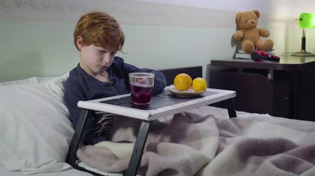 laranjas : Sad Caucasian redhead boy lying in bed and drinking hot fruit tea. Portrait of sick child staying in bedroom with bed tray. Healthcare, medicine, illness Vídeos