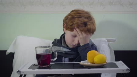 laranjas : Front view portrait of ill Caucasian boy having temperature. Sad cute kid sitting in bed in front of tray with tea and oranges. Illness, healthcare, medicine