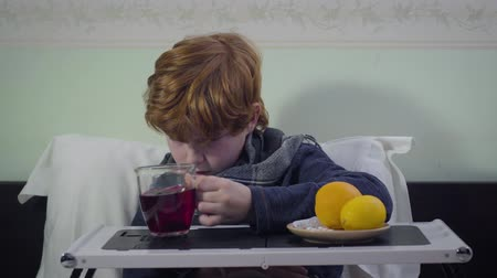 матрац : Sad Caucasian redhead kid with flu taking cup and drinking tea as sitting in bed. Cute upset unhealthy child staying at home. Medicine, sickness, healthcare Стоковые видеозаписи