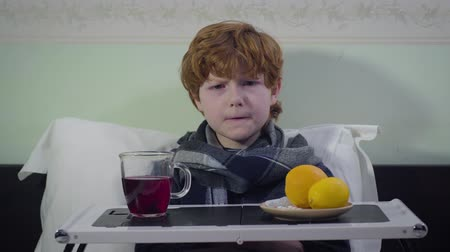 laranjas : Headshot of redhead Caucasian boy rising head and looking at camera. Dissatisfied ill kid sitting in bed at home. Healthcare, sickness, medicine Vídeos