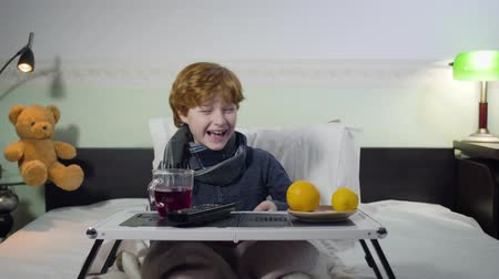 апельсины : Cheerful Caucasian redhead boy watching TV and laughing. Cute ill child sitting in bed with tray with remote control, tea, and oranges on it. Lifestyle, leisure, healthcare