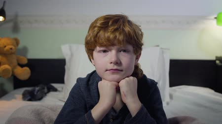 redhair : Headshot of cute Caucasian redhead kid sitting on bed and looking at camera. Portrait of little boy in his bedroom at home. Lifestyle, childhood