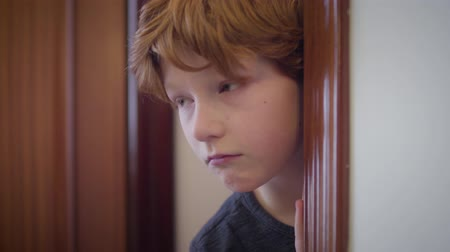 redhair : Close-up of cute redhead Caucasian boy looking out from behind doorway and hiding back. Portrait of scared little kid indoors. Fear, stress, childhood