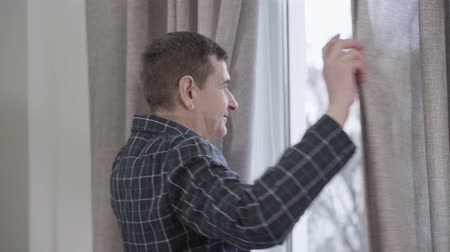 cheerfulness : Portrait of middle aged Caucasian man with earring opening curtains and looking out the window in the morning. Adult man in nightwear stretching at home. Lifestyle, leisure, enjoyment Stock Footage