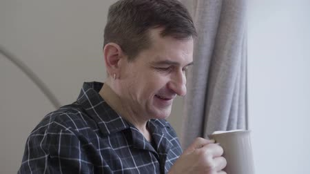 cheerfulness : Close-up face of adult Caucasian man with earring smelling and drinking morning coffee. Positive middle aged man smiling in the morning at home looking out the window. Leisure, awakening, lifestyle Stock Footage
