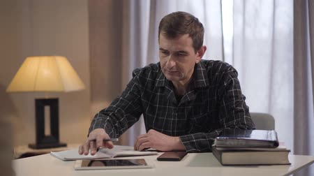 handschrift : Portrait of adult male Caucasian freelancer working at home. Middle aged man using tablet and writing down notes. Concentrated intelligent guy working distantly. Lifestyle, active seniors
