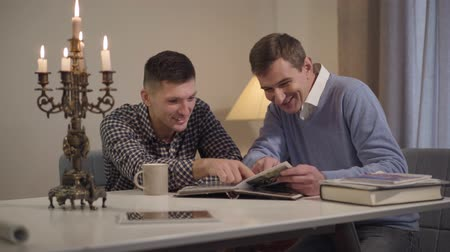 фотографий : Two adult Caucasian men sitting indoors in the evening and talking. Happy young man and his middle aged father looking at photos in album and chatting. Family, bonding, lifestyle