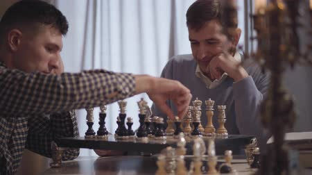 支出 : Close-up of confident Caucasian men playing chess indoors. Focus changes from adult son to middle aged father. Concentrated chessmen spending evening at home. Leisure, hobby, lifestyle