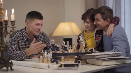 unokája : Happy Caucasian grandfather and grandson playing chess against boys father. Smiling family spending evening together at home. Leisure, lifestyle, happiness