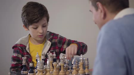 умный : Portrait of concentrated Caucasian boy playing chess and showing victory gesture. His blurred grandfather at the foreground shaking his hand. Intelligent kid winning in competition. Lifestyle, hobby Стоковые видеозаписи