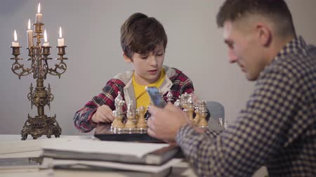šachy : Portrait of cute smart Caucasian boy placing chess on board and talking to father sitting at the foreground and using smartphone. Son asking attention from parent in the evening. Family, relationship