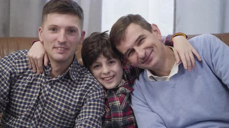 unokája : Close-up portrait of three Caucasian men of different ages looking at camera and smiling. Grandfather, son, and grandson posing indoors. Happiness, family, lifestyle Stock mozgókép