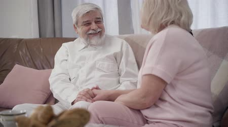 örök : Portrait of cheerful Caucasian senior man and mature woman talking and laughing at home. Happy joyful couple of retirees spending evening together indoors. Love, marriage, happiness, joy