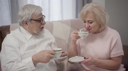 örök : Close-up portrait of old Caucasian man and woman drinking tea at home. Happy mature spouses spending evening together indoors. Lifestyle, retirement, leisure