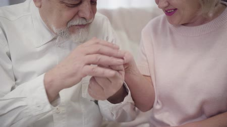 pocałunek : Close-up of old Caucasian elegant man kissing wifes hand. Senior couple in love spending time together. Happy retirees enjoying evening at home. Eternal love, happiness, marriage