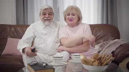 örök : Portrait of positive mature Caucasian couple in love watching TV in the evening. Happy senior husband and wife resting together indoors. Leisure, happiness, lifestyle, eternal love concept