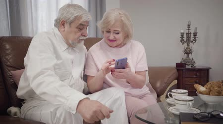 örök : Modern senior Caucasian woman teaching her elegant husband to use smartphone. Intelligent mature female retiree sitting with phone and talking with spouse. Retirement. modern technologies, support Stock mozgókép