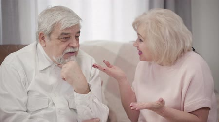 disputa : Close-up of emotional mature Caucasian woman scolding elderly husband at home. Displeased couple of retirees arguing indoors in the evening. Misunderstanding, conflict, dispute