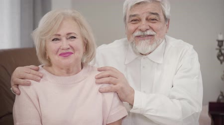 örök : Elderly Caucasian couple talking to each other, looking at camera and smiling. Positive married retirees posing indoors. Love, happiness, lifestyle Stock mozgókép