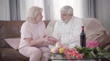 elkötelezettség : Happy mature Caucasian spouses spending Saint Valentines Day at home. Senior couple holding hands and talking in front of the table with flowers, wine and gift box. Bonding, eternal love, happiness