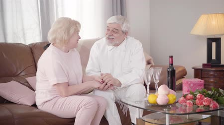 pocałunek : Portrait of senior Caucasian elegant man kissing womans hand and talking with wife on Saint Valentines Day. Happy old couple in love celebrating holiday at home. Lifestyle, bonding, eternal love