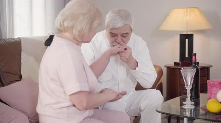 pocałunek : Middle shot of happy Caucasian mature man kissing wifes hand and looking at woman with love. Married couple celebrating Saint Valentines Day at home. Holiday, romance, eternal love Wideo