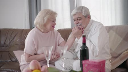 pocałunek : Side view of beautiful Caucasian elderly woman caressing husbands face and looking at him with love. Happy mature man kissing wifes hand and smiling. Romance, joy, eternal love concept